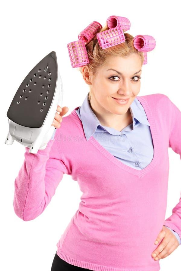 Женщина при ролики волос держа утюг стоковое изображение rf