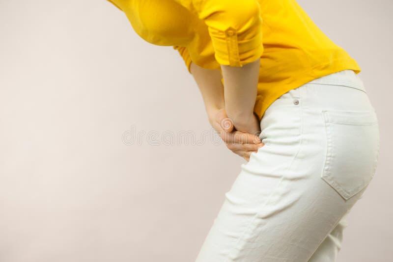Женщина при руки держа ее crotch стоковое изображение