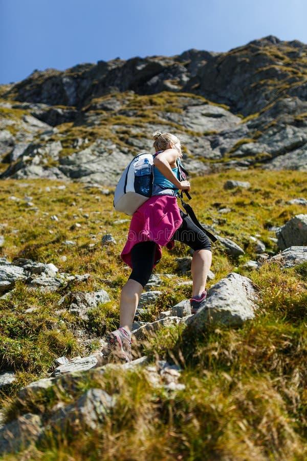 Женщина при рюкзак на следе стоковая фотография