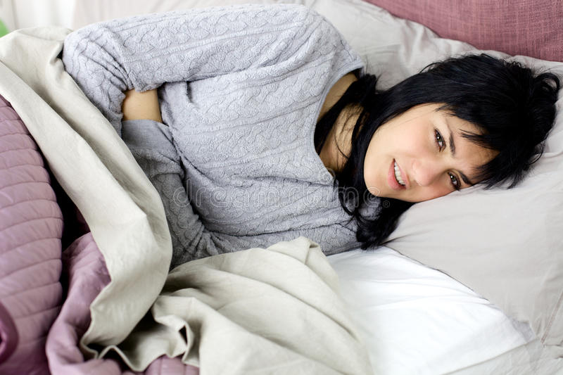 Женщина при сильная боль в животе менструации лежа в кровати стоковые фото