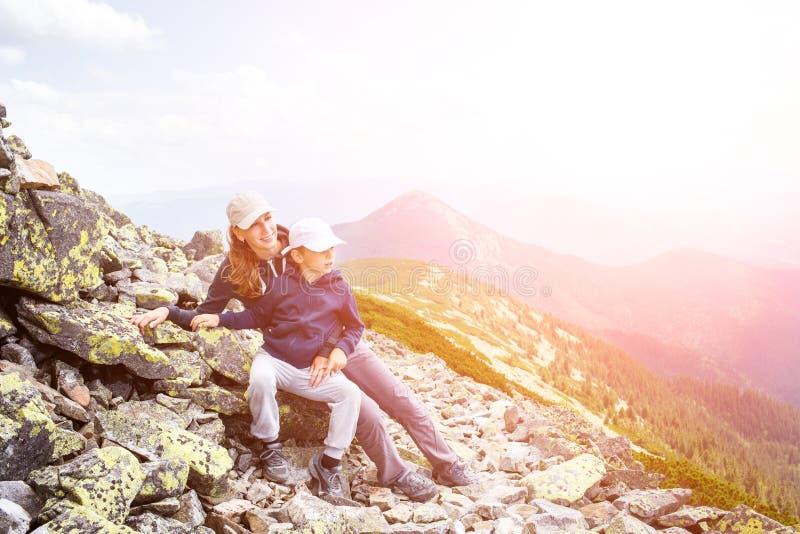 Женщина при сын отдыхая на большом камне в горах стоковая фотография rf