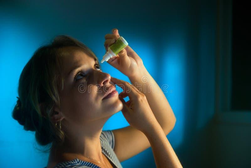 Женщина при утомлянные глаза прикладывающ падения глаза Collyrium стоковая фотография rf