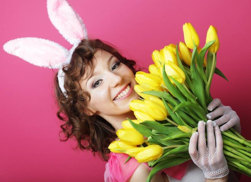 Женщина при уши зайчика держа желтые тюльпаны стоковые изображения rf