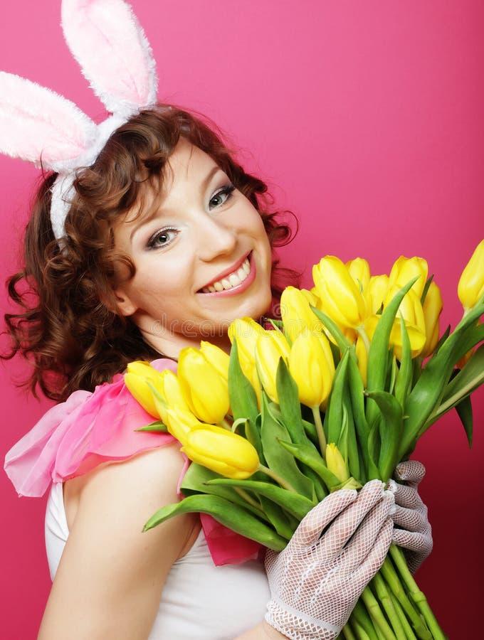 Женщина при уши зайчика держа желтые тюльпаны стоковое изображение
