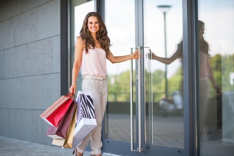 Женщина при хозяйственные сумки входя в магазин стоковое фото rf