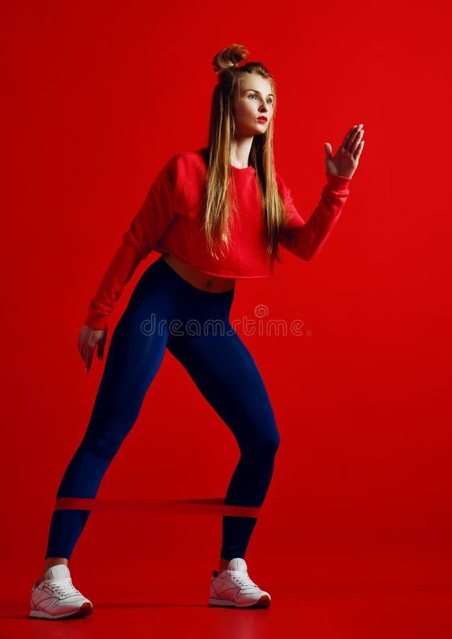 Женщина при хорошие физические данные делая протягивать разрабатывает с эластичными резиновыми лентами стоковая фотография rf
