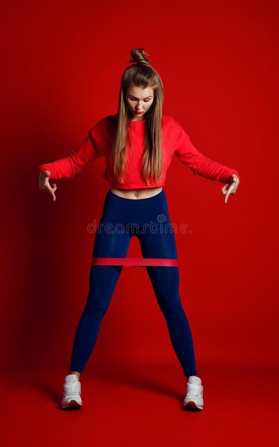 Женщина при хорошие физические данные делая протягивать разрабатывает с эластичными резиновыми лентами стоковая фотография