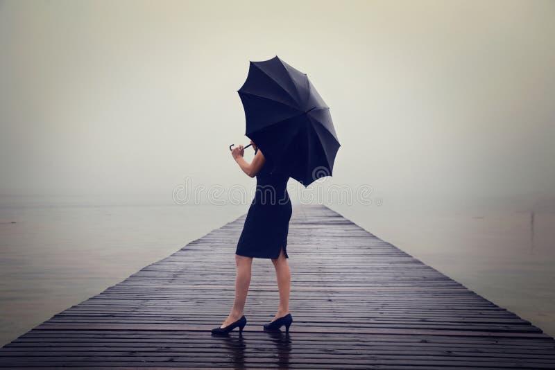 Женщина при черный зонтик смотря безграничность в сюрреалистическом месте стоковые фотографии rf
