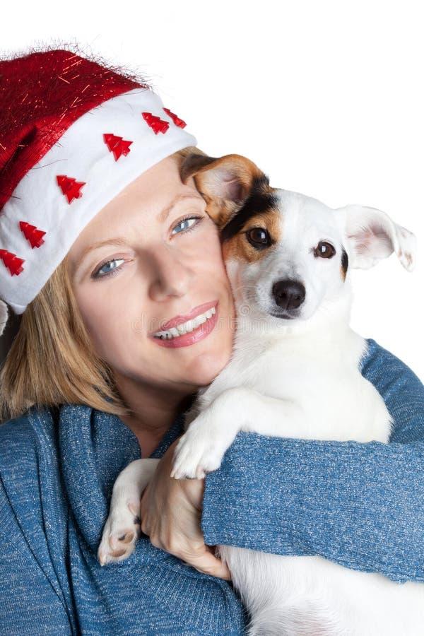 Женщина при шляпа рождества обнимая ее собаку стоковые фотографии rf
