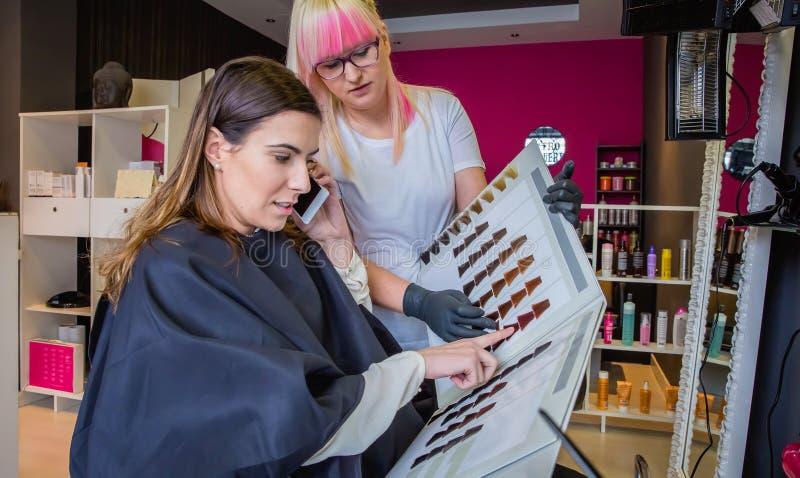Женщина при smartphone смотря палитру краски волос стоковое фото rf