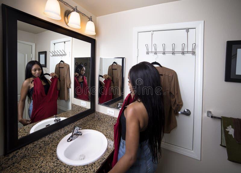 Женщина пробуя на одеждах смотря зеркало в ванной комнате стоковая фотография