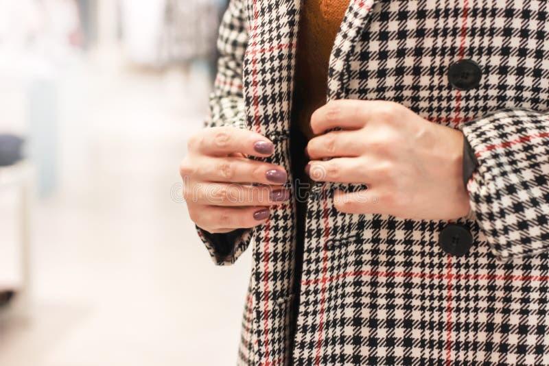 Женщина пробуя на пальто в клетке в магазине стоковое изображение rf