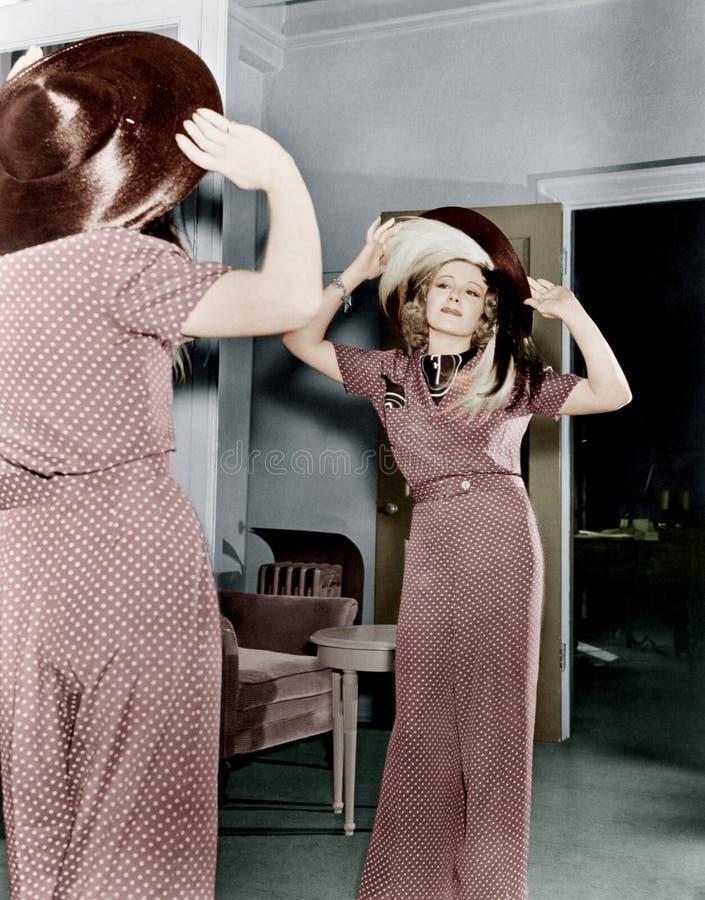 Женщина пробуя на шляпе (все показанные люди более длинные живущие и никакое имущество не существует Гарантии поставщика что буде стоковое изображение rf