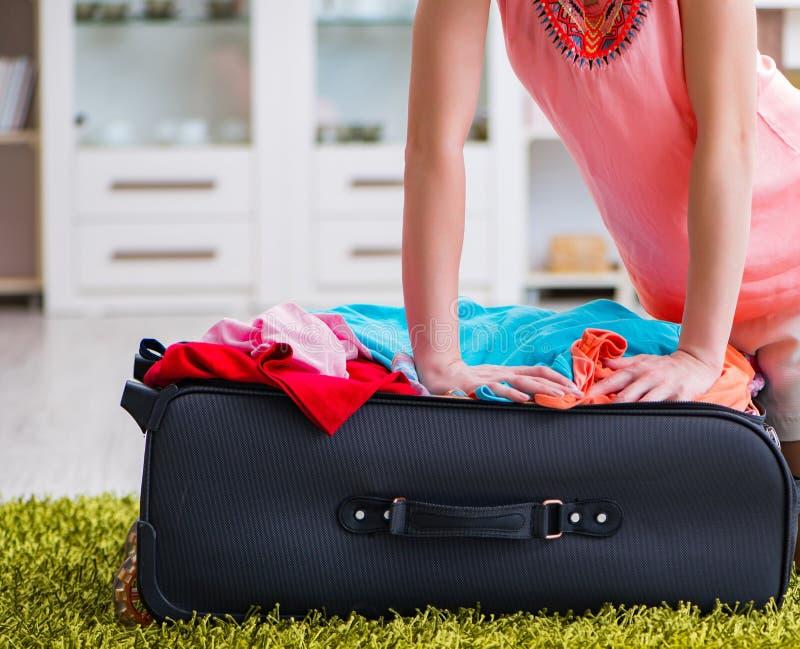 Женщина пробуя приспосабливать всю одежду к suitacase перед каникулами стоковые фото