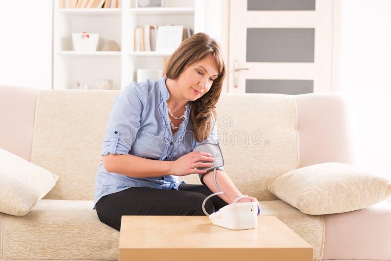 Женщина проверяя ее кровяное давление стоковые изображения rf