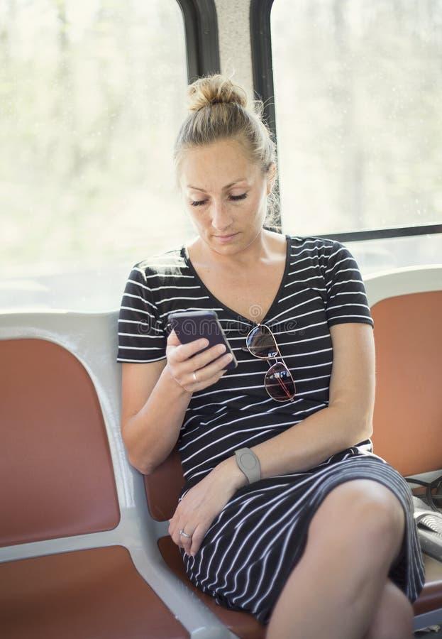 Женщина проверяя ее умный телефон пока едущ поезд или шина стоковая фотография rf