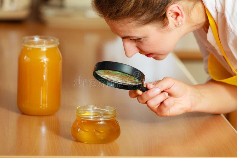 Женщина проверяя мед с лупой стоковые фотографии rf
