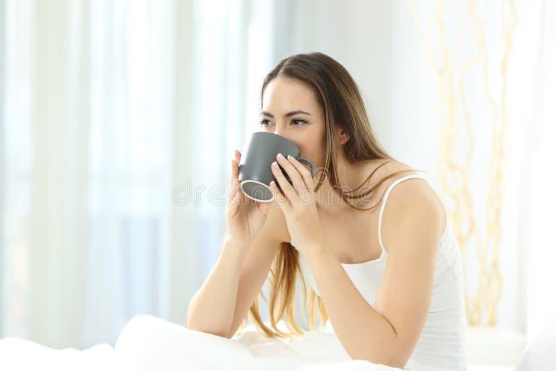 Женщина просыпая вверх выпивая кофе на кровати стоковые фотографии rf