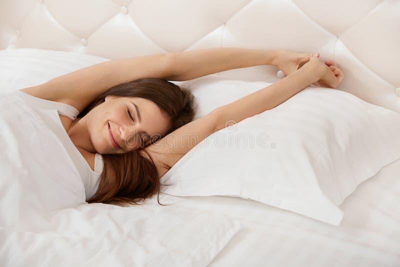 Женщина протягивая в ее кровати Девушка просыпая вверх в утре стоковые изображения