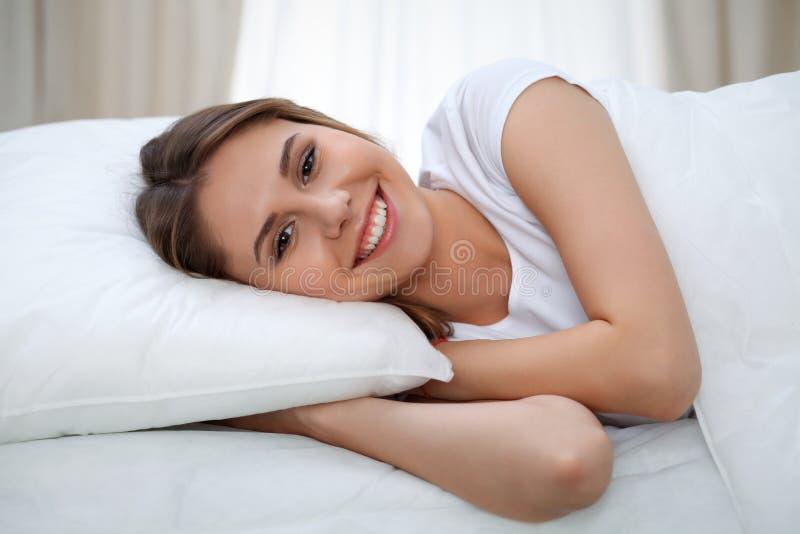 Женщина протягивая в кровати после бодрствования вверх, входящ в день счастливый и расслабленный после сна спокойной ночи Сладост стоковое фото