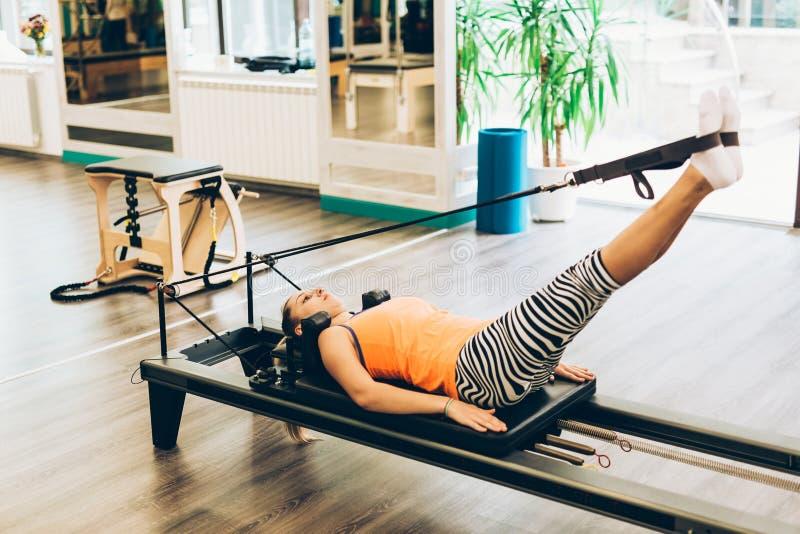 Женщина протягивая в реформаторе pilates стоковые фотографии rf