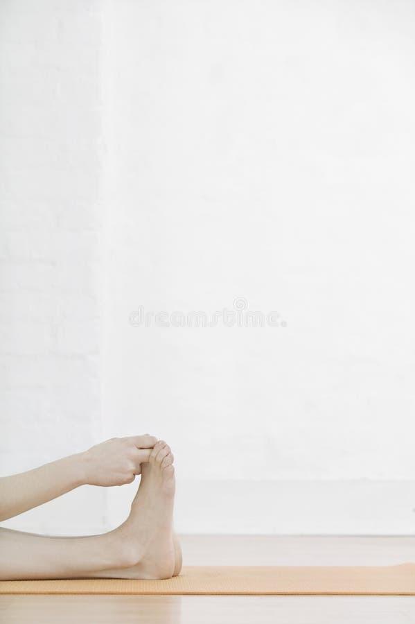 Женщина протягивая ее мышцы ноги стоковая фотография