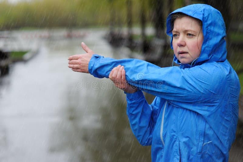 Женщина протягивая оружия перед разминкой в дожде стоковое фото