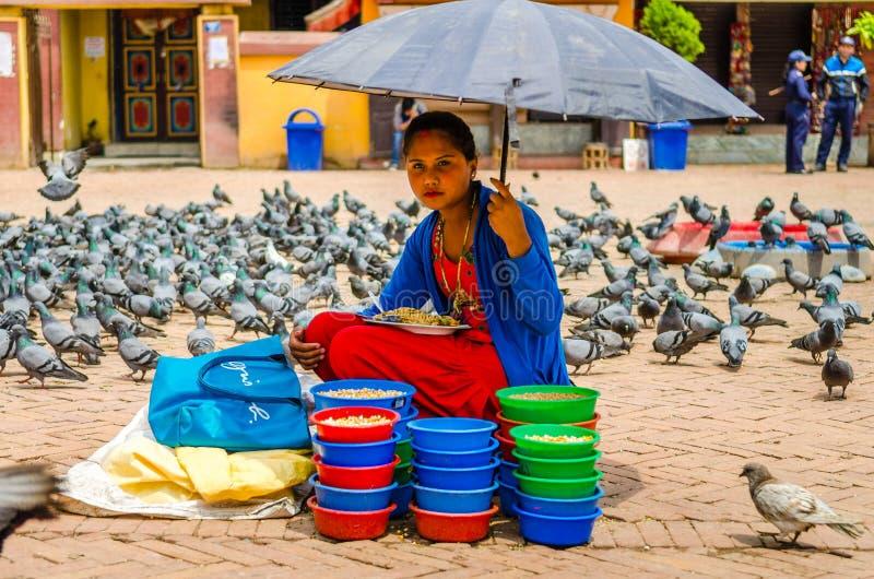 Женщина продает еду для голубей вокруг stupa Boudhnath стоковая фотография