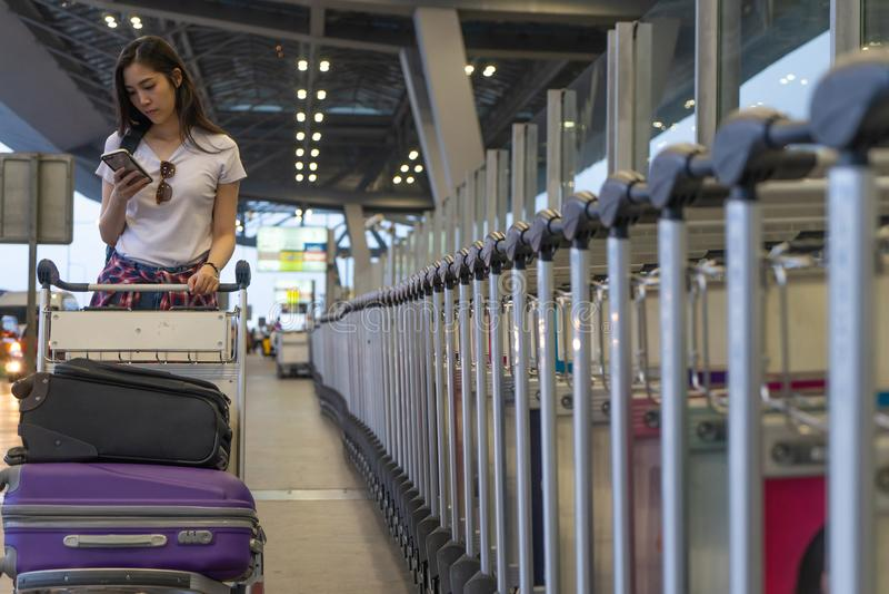 Женщина путешественника в крупном аэропорте используя мобильный смартфон с багажом и сумка на тележке вагонетки аэропорта Молодой стоковое изображение rf