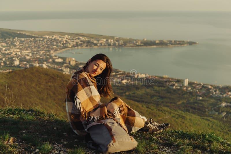 Женщина путешественника обернутая в отдыхать шотландки внешний стоковое изображение