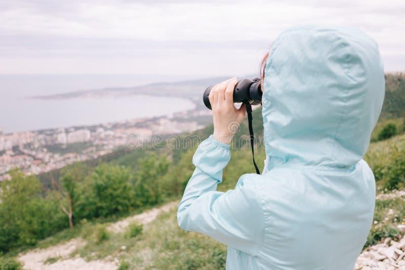 Женщина путешественника смотря через бинокли на заливе моря стоковое изображение