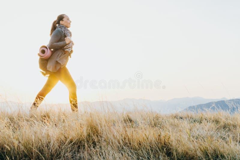 Женщина путешественника с рюкзаком и циновкой йоги идя вдоль дороги стоковые фото