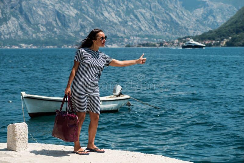 Женщина путешествовать на пристани Девушка ждет шлюпку на пристани стоковое изображение