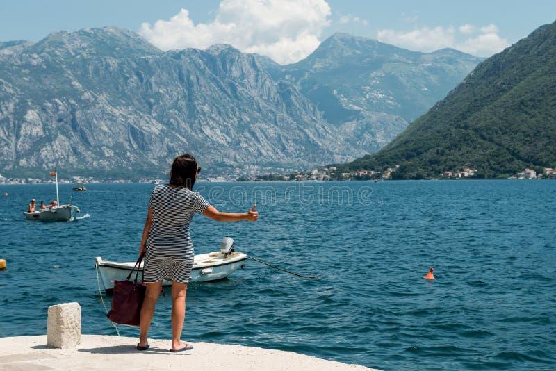 Женщина путешествовать на пристани Девушка ждет шлюпку на пристани стоковая фотография rf