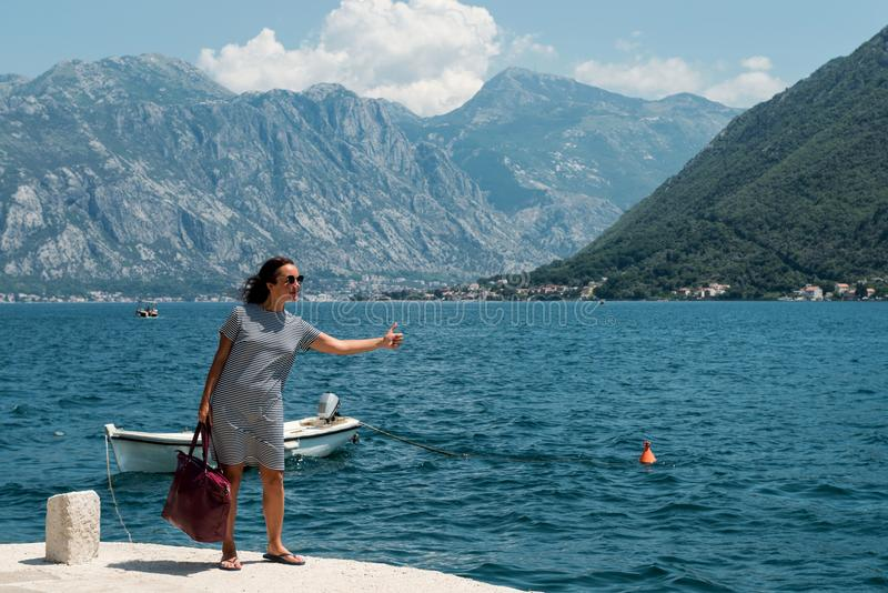 Женщина путешествовать на пристани Девушка ждет шлюпку на пристани стоковое фото