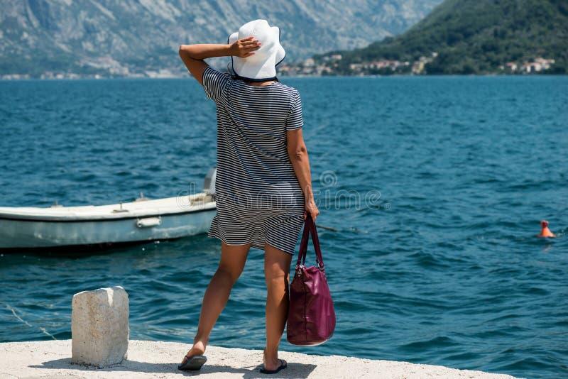 Женщина путешествовать на пристани Девушка ждет шлюпку на пристани стоковые фотографии rf