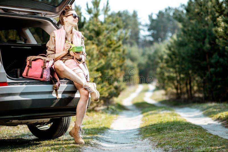 Женщина путешествуя на автомобиле в лесе стоковые фото