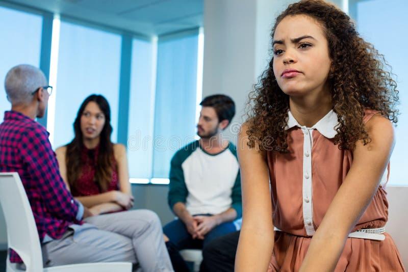 Женщина плача пока творческая команда дела в предпосылке стоковые изображения rf