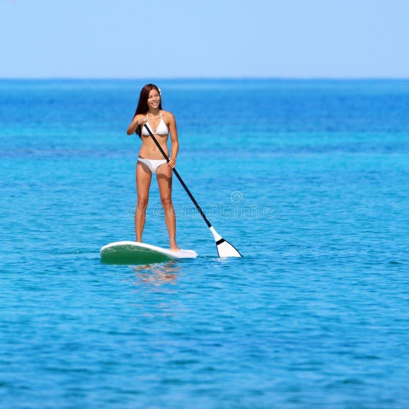 Женщина пляжа Paddleboarding дальше стоит вверх paddleboard стоковые фото