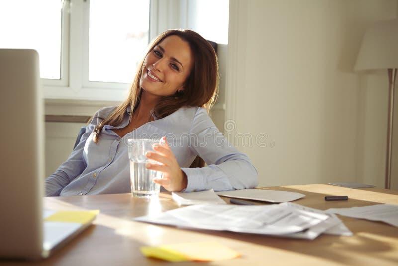Женщина работая в домашнем офисе усмехаясь на камере стоковые фото