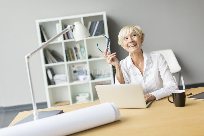 Женщина работая в офисе стоковое фото rf