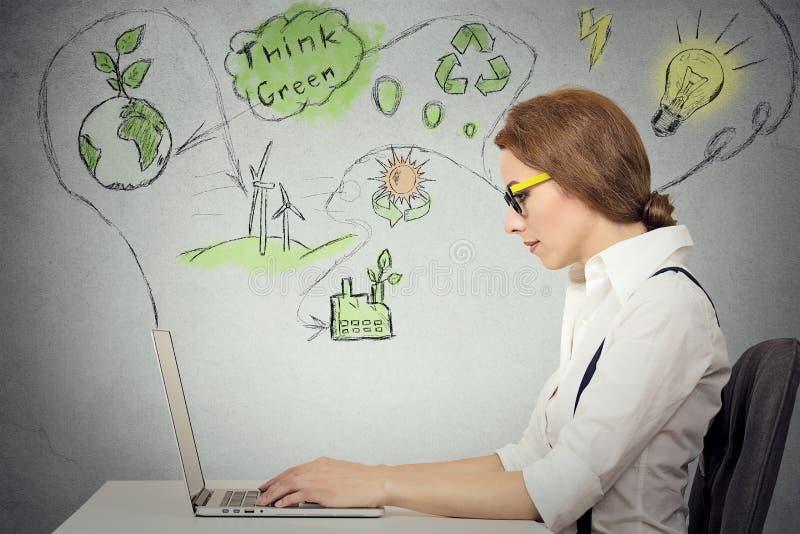 Женщина работая на компьютере разрешая экологичность, проблему возобновляющей энергии стоковое фото rf