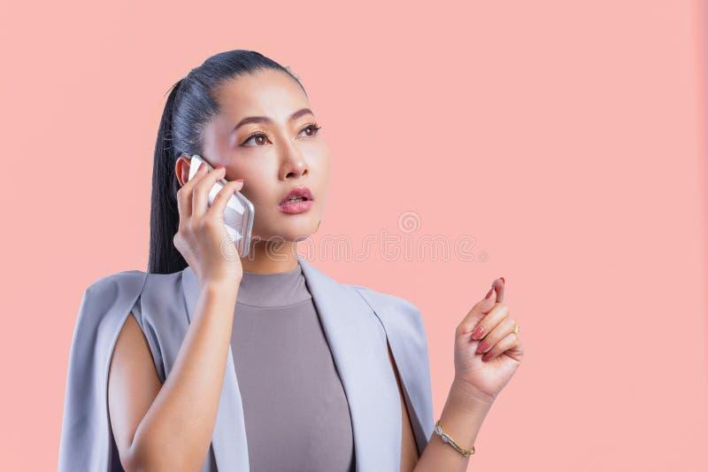 Женщина работая на ноутбуке на офисе пока говорящ по телефону стоковая фотография