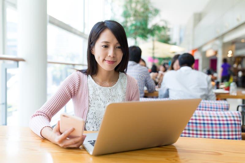 Женщина работая на портативном компьютере и используя мобильный телефон стоковое фото