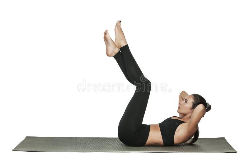 Женщина работая на циновке йоги Изолировано на белизне стоковые фото