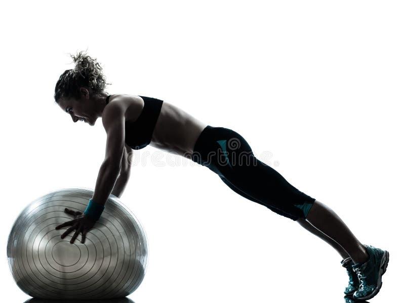 Женщина работая разминку шарика фитнеса   силуэт стоковые изображения