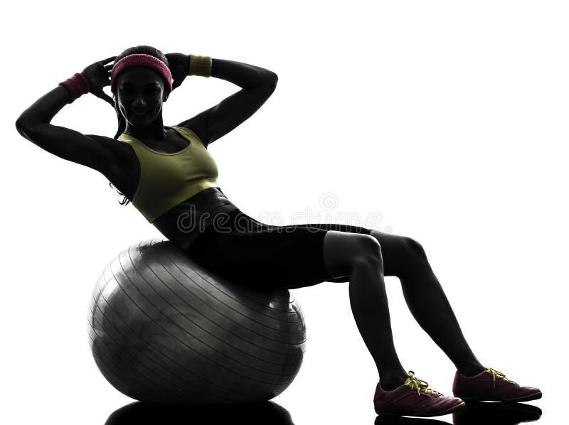 Женщина работая силуэт разминки шарика фитнеса хрустов стоковое фото