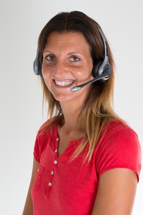 женщина работы с клиентом с наушниками в офисе на серой предпосылке стоковая фотография rf