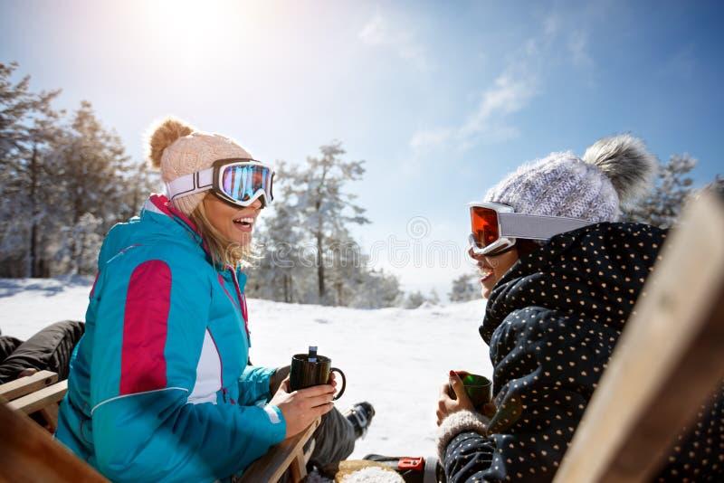 Женщина 2 разговаривая с напитком в sunbed на местности лыжи стоковые фото