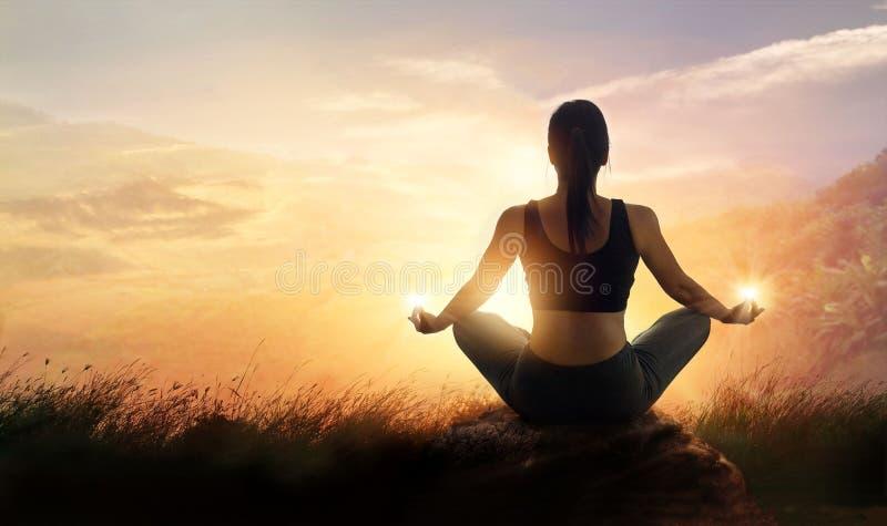 Женщина размышляя йога на горах захода солнца с природой Внешний s стоковые фотографии rf